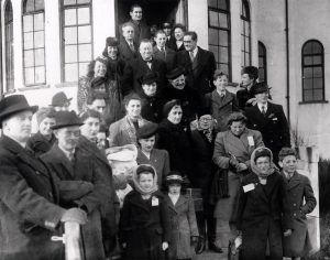 Group of adults and evacuee children on steps of a building in Brighton during the Second World War
