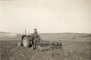 A land girl operating a tractor