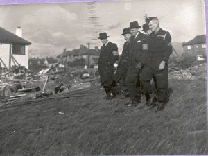 Five members of the Civil Defence walking down a hill.