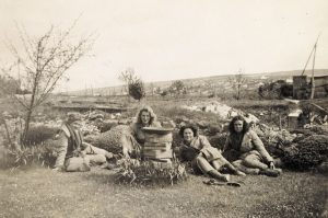 Four members of the Women's Land Army sit around what could be a brick oven, 1941