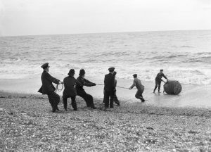 Royal Navy bomb disposal team with police removing a mine from the sea at Brighton beach c.1945